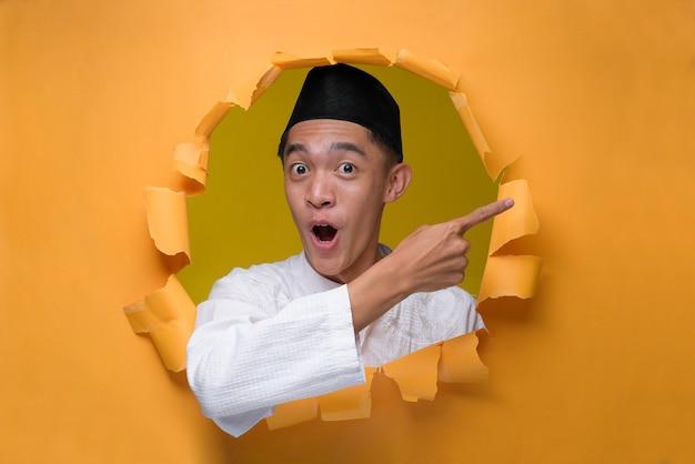 Asiatischer muslimischer mann posiert durch zerrissenes gelbes papierloch mit geschocktem gesicht, trägt muslimisches tuch mit schädelkappe und zeigt einen kopienraum, um etwas zu präsentieren.