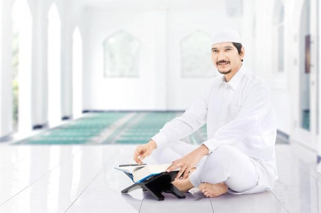 Asiatischer muslimischer mann sitzt und liest den koran