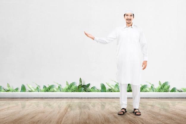 Asiatischer muslimischer mann stehend und offene handfläche zeigend