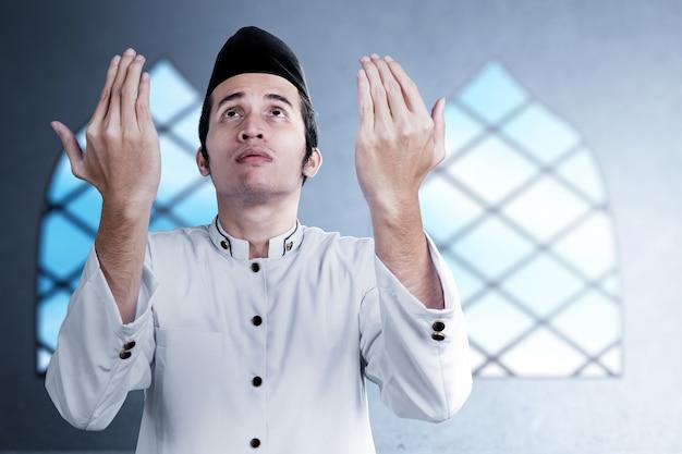 Asiatischer muslimischer mann stehend, während erhobene hände und auf der moschee betend