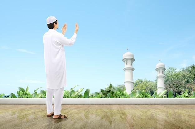 Asiatischer muslimischer mann stehend, während erhobene hände und beten