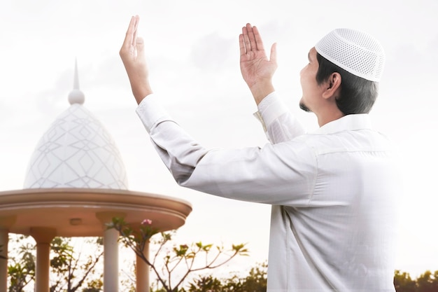 Asiatischer muslimischer mann stehend, während erhobene hände und betend