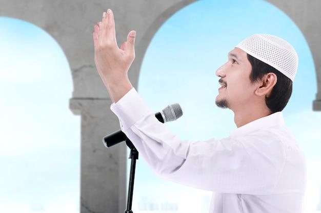 Asiatischer muslimischer mann stehend, während erhobene hände und eine predigt auf der moschee halten