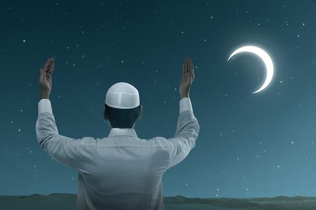 Asiatischer muslimischer mann stehend, während erhobene hände und mit der nachtszene betend