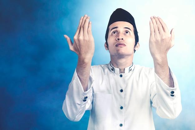 Asiatischer muslimischer mann stehend, während erhobene hände und mit einem farbigen hintergrund beten
