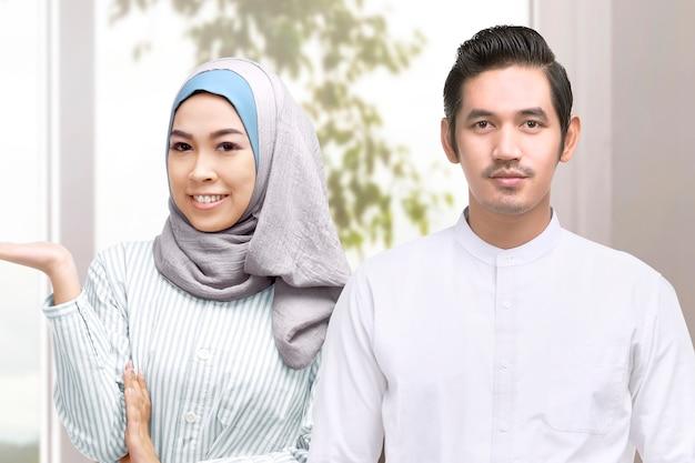 Asiatischer muslimischer mann und frau in einem schleier, der etwas zu hause zeigt. leerer bereich für kopienraum