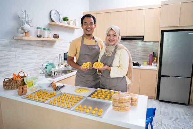 Asiatischer muslimischer mann und frau mit backblech des nastar-snacks