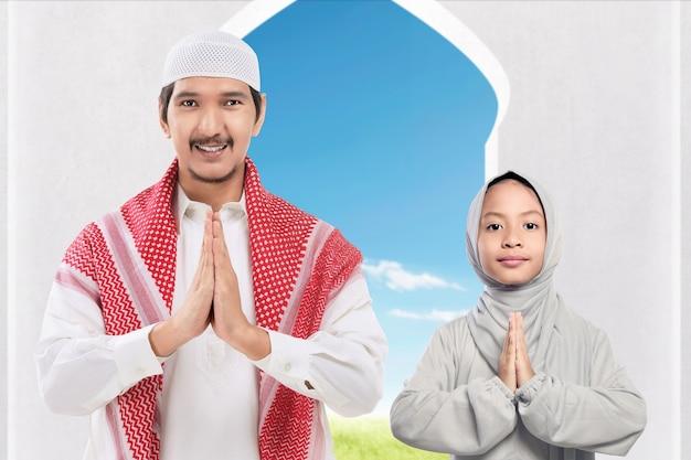 Asiatischer muslimischer mann und mädchen, die mit grußgeste auf der moschee stehen