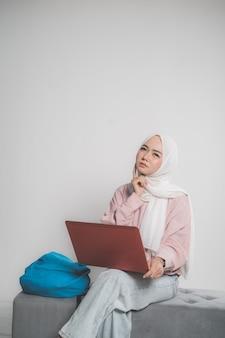 Asiatischer muslimischer student, der laptop vor weißem lokalisiertem hintergrund hält, der oben sitzt und denkt