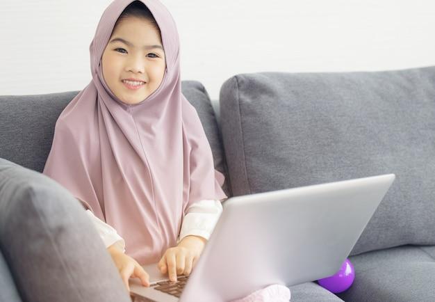 Asiatischer muslimischer teenager, der internet mit notizbuch auf sofa im wohnzimmer surft