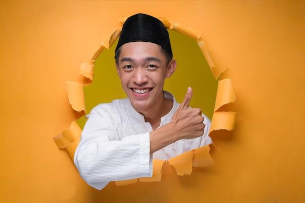 Asiatischer muslimischer teenager-mann, der in die kamera mit daumen bis zum kopieren von sapce lächelt, posiert durch zerrissenes gelbes papierloch und trägt muslimisches tuch mit schädelkappe.