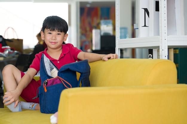 Asiatischer netter junge, der auf gelbem sofa innerhalb der tutorschule sitzt.