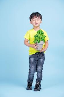 Asiatischer niedlicher kleiner hübscher junge halten einen topf der grünen pflanze und lächeln, umweltfreundliches konzept