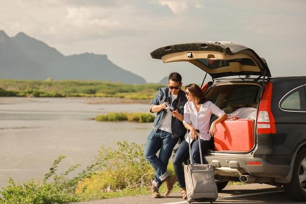 Asiatischer paar mann mit der weinlesekamera und -frau, die ein zurück vom auto sitzen, reisen zum berg und zum see im feiertag mit autoautoreise