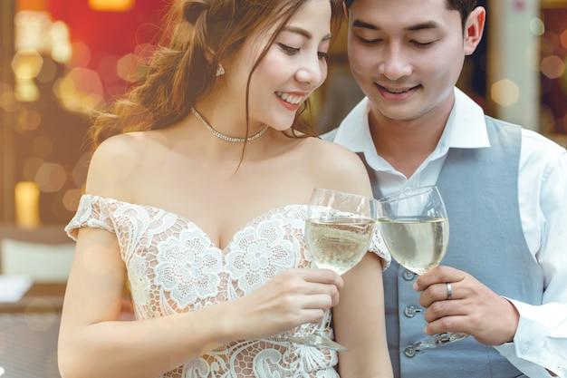 Asiatischer paarbeifall, der zusammen im restaurant trinkt.