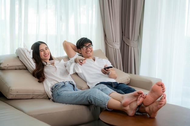 Asiatischer paarlebensstil, mann, der fernbedienung hält und frau, die zu hause fernsehfilme aufpasst