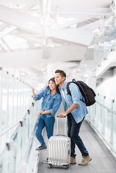 Asiatischer paarreisender mit gepäck am flughafen