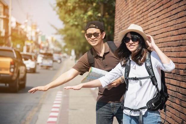 Asiatischer paartourist, der den stadtplan kreuzt die straße hält