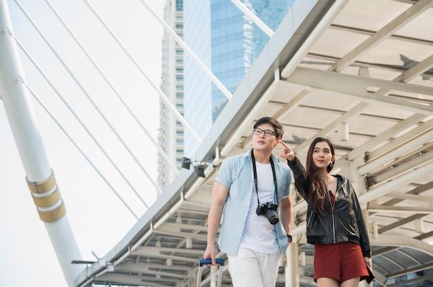 Asiatischer paartourist, der finger für richtung und reisen in der stadtstadt sucht und zeigt.