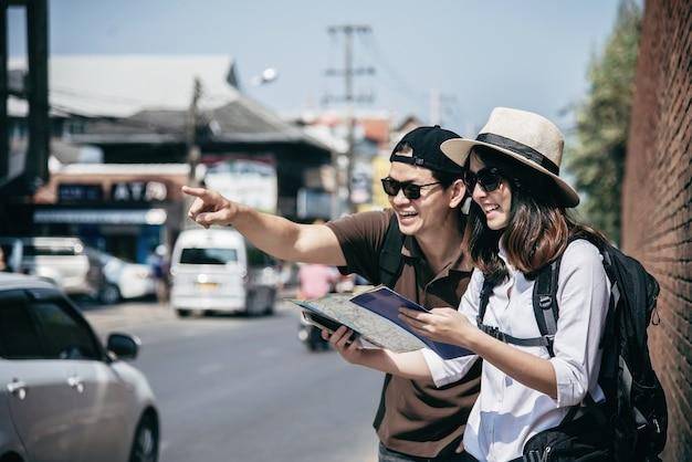 Asiatischer paartourist, der stadtplan hält