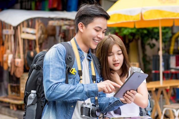Asiatischer paartourist, der tablette verwendet, um standort beim reisen in bangkok zu finden