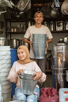 Asiatischer paarverkäufer, der lächelt, während er den eimer im haushaltsgerätegeschäft hält