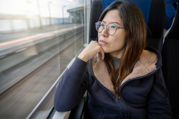 Asiatischer passagier junger dame, der in einer deprimierten stimmung neben dem fenster innerhalb des zugs sitzt