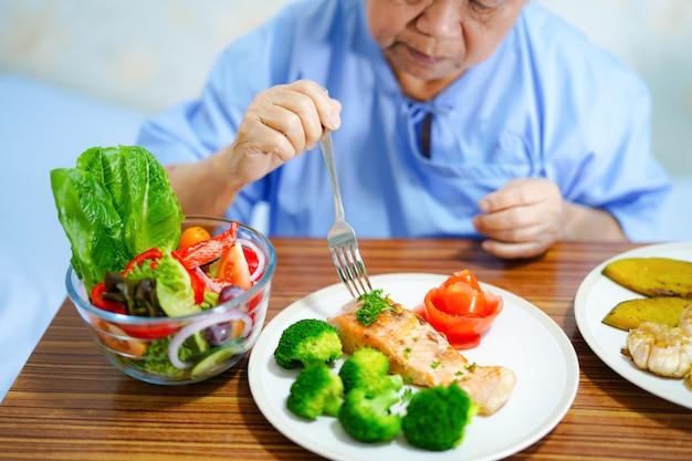 Asiatischer patient der alten frau, der gesundes lebensmittel isst.