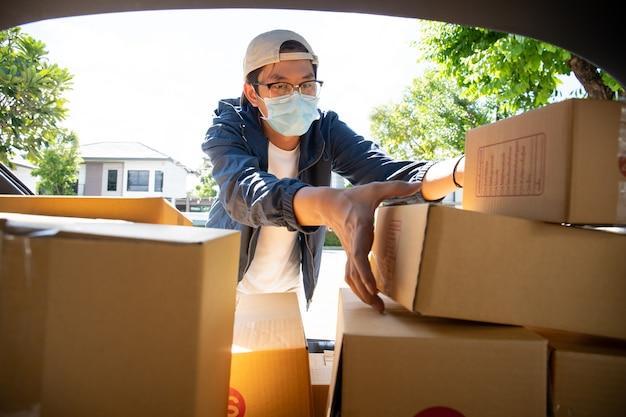 Asiatischer postbote mit einer hygieneschutzmaske, die eine paketverpackung aufnimmt