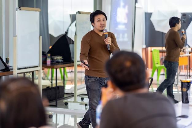 Asiatischer referent oder vortrag im ungezwungenen anzug auf der bühne vor der raumpräsentation