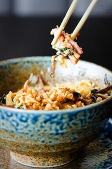 Asiatischer reis mit schweinefleisch, mu-err-pilzen, napa-kohl, eingelegten bambussprossen, spinat, teriyaki, süßen chili-sauce, zwiebelchips in keramikschale.