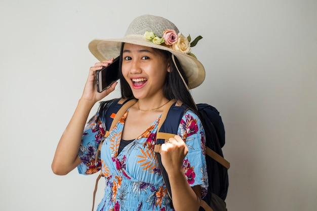Asiatischer reisender, der auf dem handy spricht. sommerreisekonzept über weißem hintergrund