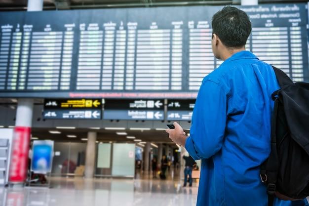 Asiatischer reisender, der das intelligente mobiltelefon für das einchecken am fluginformationsschirm verwendet