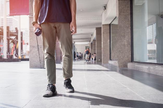 Asiatischer reisender des jungen mannes, der im urlaub am kaufhaus erforscht stadt bangkoks thailand geht