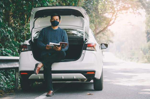 Asiatischer reisender mann, der gesichtsmaske trägt und ein buch mit offenem autokofferraum liest