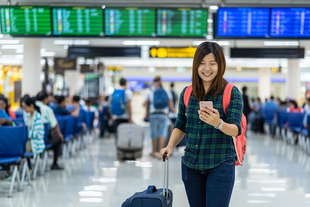 Asiatischer reisender mit dem gepäck, das den intelligenten handy für abfertigung über dem flug bo hält