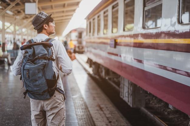 Asiatischer reisender mit rucksack in der bahn, rucksack und hut am bahnhof mit einem reisenden. reisekonzept. mann reisender tourist zu fuß am bahnhof.