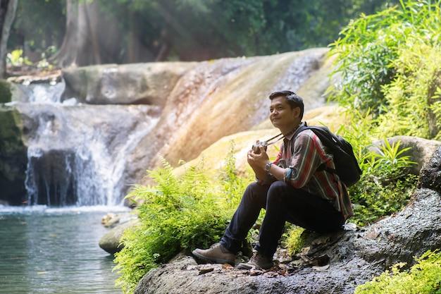 Asiatischer reisendmann mit dem rucksack, der kamera mit grünem natürlichem hintergrund hält.