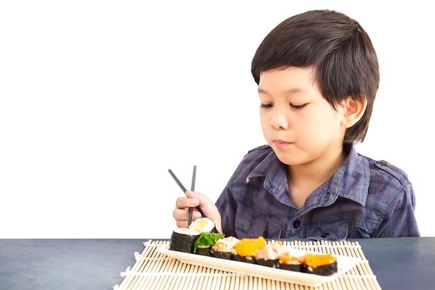 Asiatischer reizender junge isst die sushi, die über weißem hintergrund lokalisiert werden