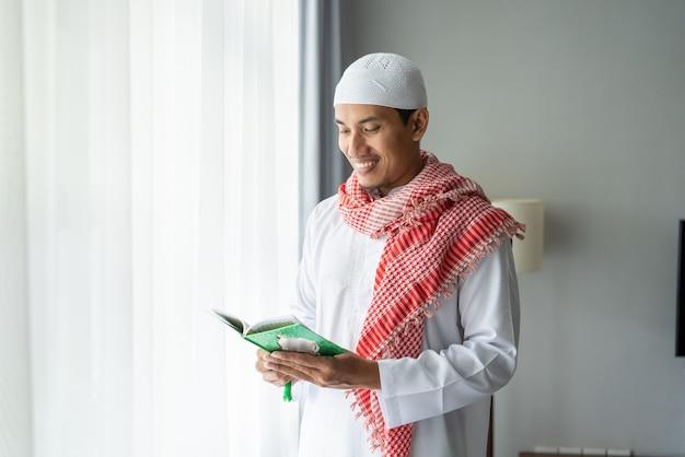 Asiatischer religiöser mann, der koran oder koran liest, während er neben dem fenster steht