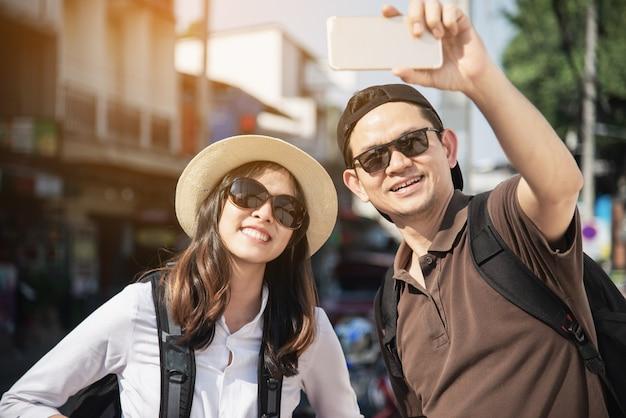 Asiatischer rucksackpaartourist, der den stadtplan kreuzt die straße hält - reiseleute-ferienlebensstilkonzept
