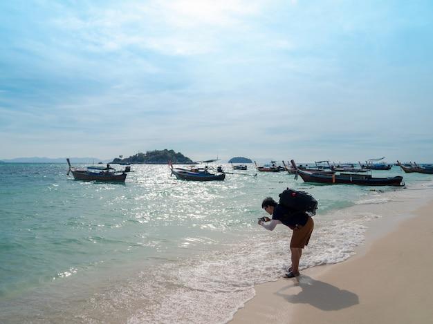 Asiatischer rucksacktourist, der seewelle mit smartphone am sonnigen strand mit sonnenlichtreflexion auf der wasseroberfläche auf der insel lipe, thailand, fotografiert, mann entspannt sich im sommer im urlaub