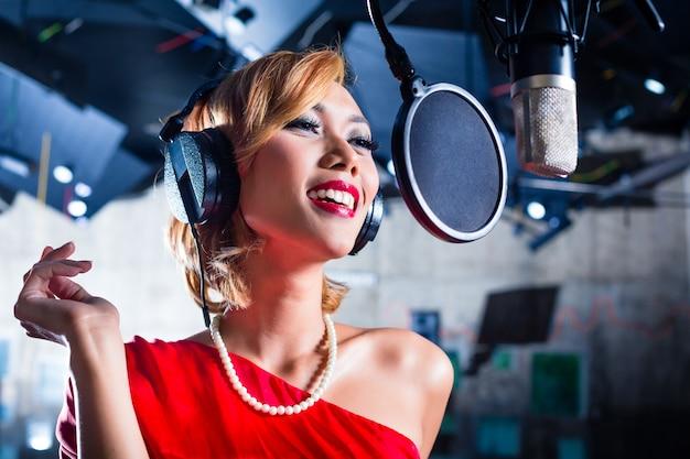 Asiatischer sänger, der lied im tonstudio produziert
