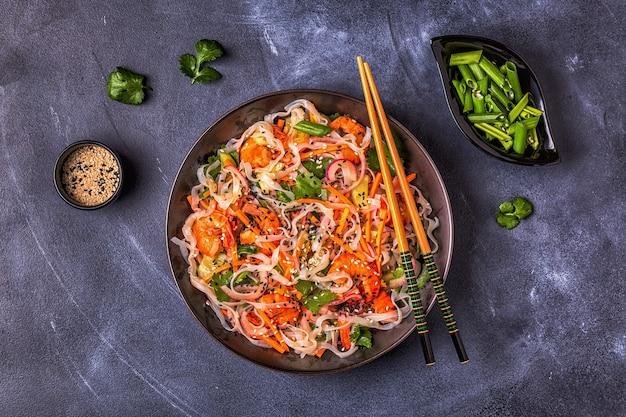 Asiatischer salat mit reisnudeln, garnelen und gemüse, draufsicht.