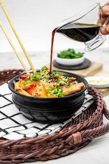 Asiatischer salat mit reisnudeln, gemüse, champignons, hühnerfleisch und sojasauce. funchose mit weißen transparenten nudeln im schwarzen teller