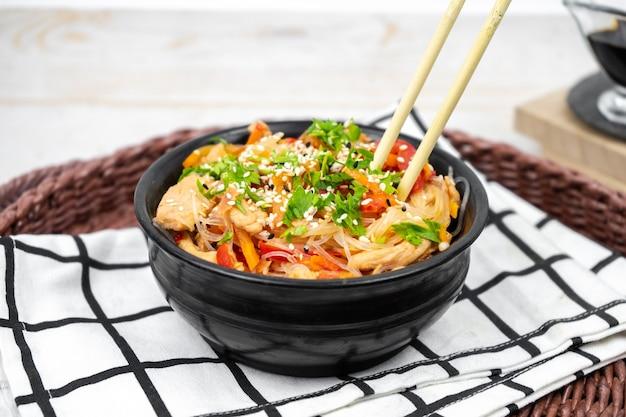 Asiatischer salat mit reisnudeln, gemüse, champignons, hühnerfleisch und sojasauce mit stäbchen