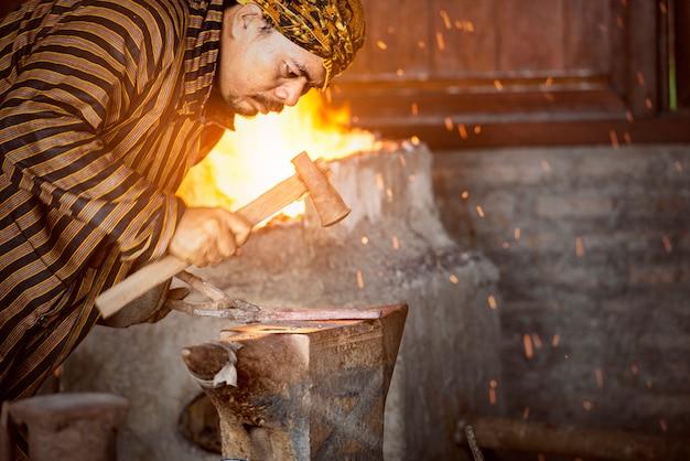 Asiatischer schmied, der das flüssige metall mit einem hammer schmiedet, um keris zu machen