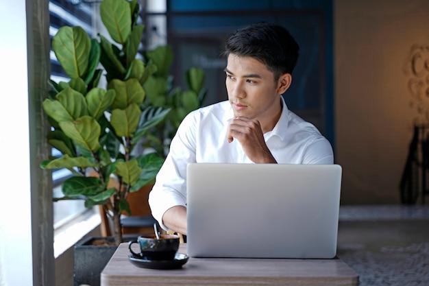 Asiatischer schöner geschäftsmann oder büroangestellter, der am kaffeehaus arbeitet