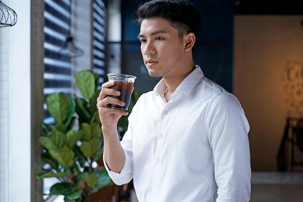 Asiatischer schöner geschäftsmann oder büroangestellter oder junger student, der kaffee am caféladen trinkt
