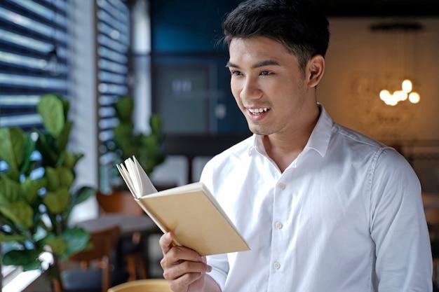 Asiatischer schöner geschäftsmann oder büroangestellter oder junger student, der notizbuch oder buch liest